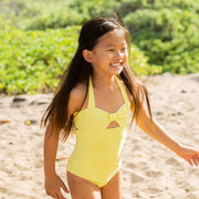girl wearing yellow eco-friendly swimsuit running on the beach