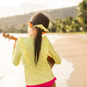 Girl wearing yellow rash guard with ruffles