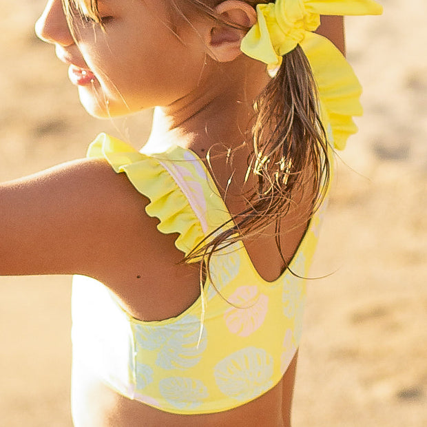Girls two piece eco-friendly reversible yellow bikini swimsuit with ruffle detail.