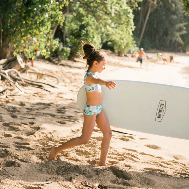 girl wearing eco friendly swimsuit carrying surfboard