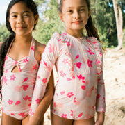 Two girls wearing eco-friendly swimwear in pink floral design locking arms on the beach