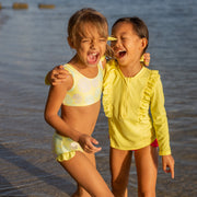 Two girls laughing on a beach wearing eco-friendly swimsuits in yellow