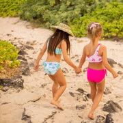 girls wearing sustainable two piece reversible bikinis holding hands on beach