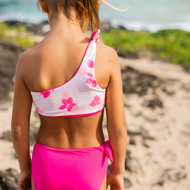 Back view of girl wearing reversible swimsuit in pink