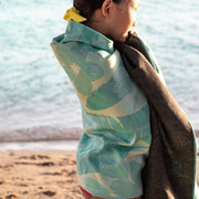 Eco-friendly beach towel wrapped around girl on beach