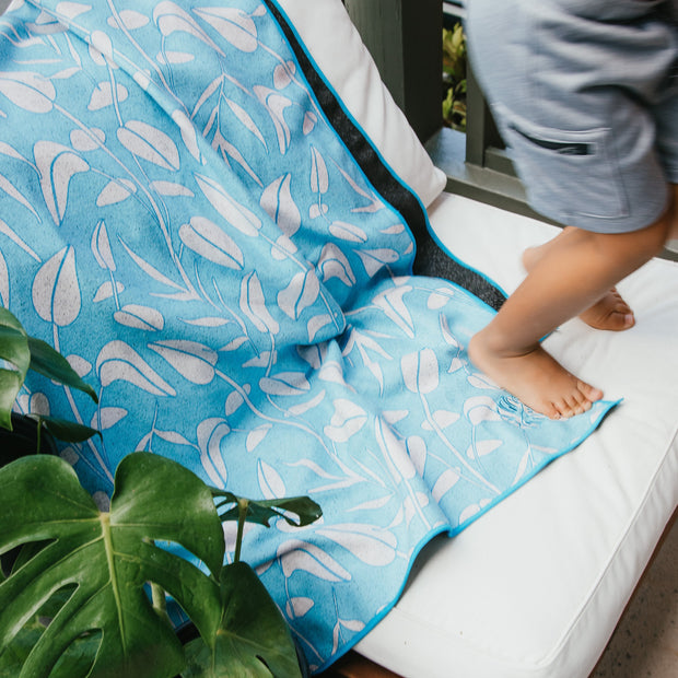 Eco-Friendly blue floral beach towel on chair with boy