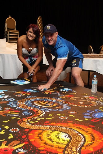 Chern'ee paints with the NRL's All Stars Team