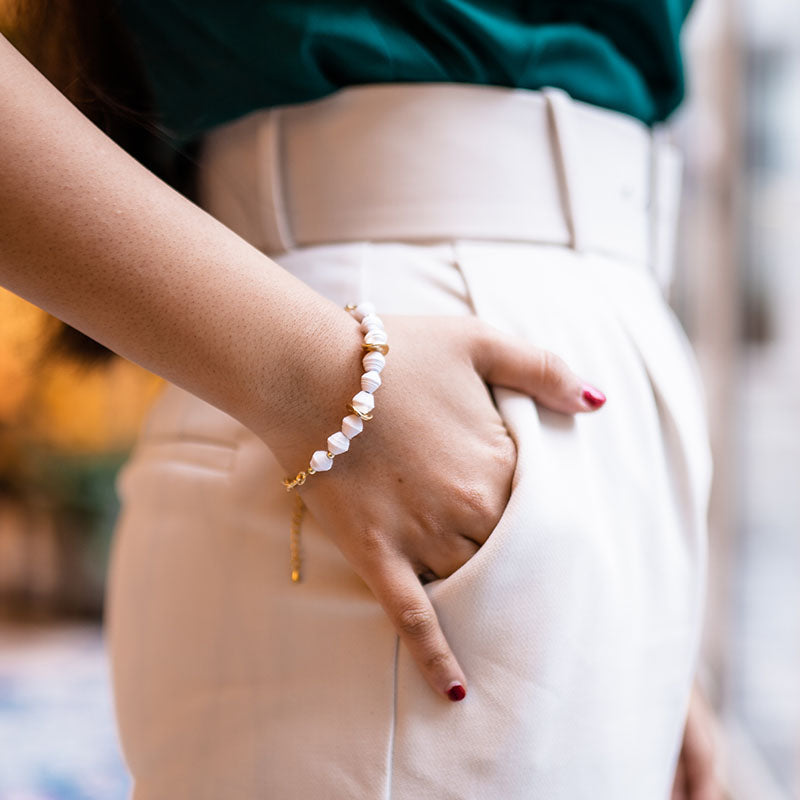 Woman wearing ethically made 18k gold plated bracelet with white paper beads on hand