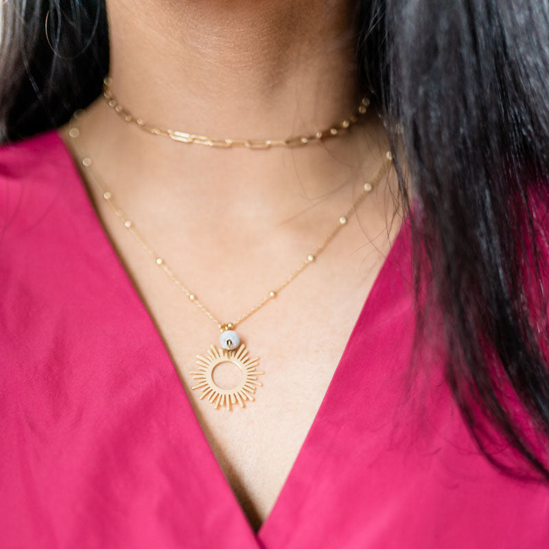Woman wearing 18k gold plated necklace with sun pendant and paper bead close up