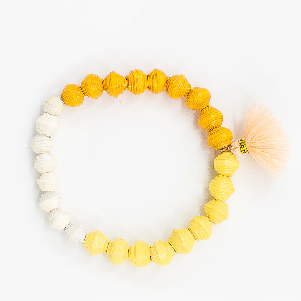 The Jetsetter Tassel Bracelet: yellow and orange handmade paper bead bracelet with tassel made by artisans in the Horn of Africa. Sustainable, Artisan-Made And Ethically Sourced