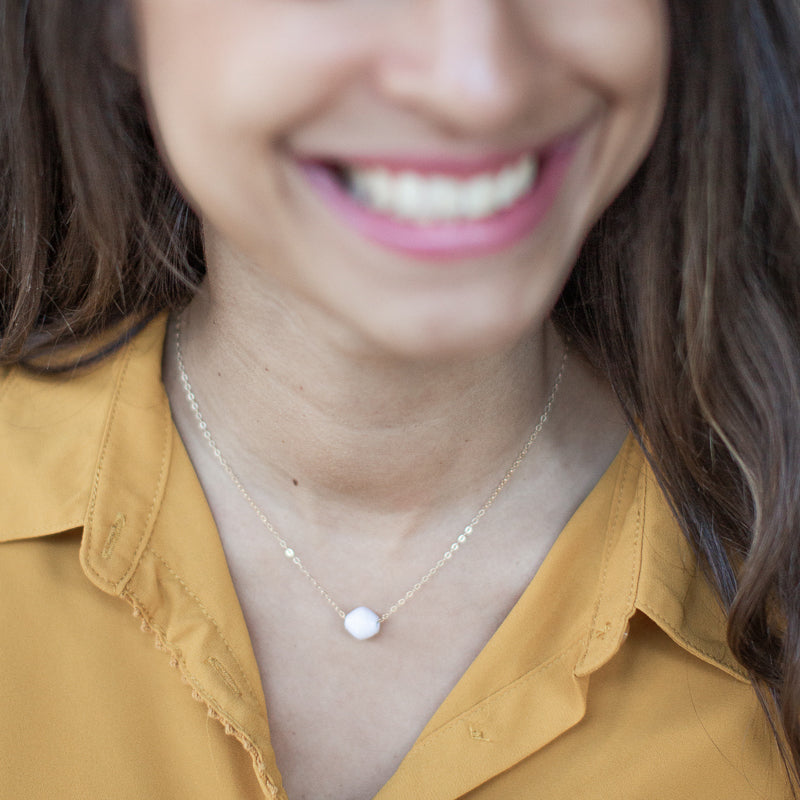 The Dainty Drop Necklace: white handmade paper bead on 14k gold filled chain necklace made by artisans in the Horn of Africa. Sustainable, Artisan-Made And Ethically Sourced