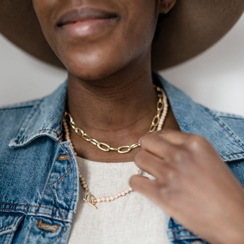 Woman wearing ethically made layered necklaces with 18k gold plated toggle and cream paper beads close up
