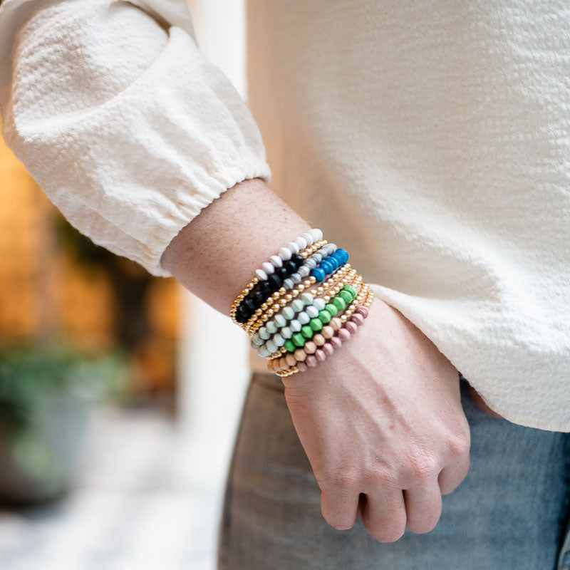 Woman wearing stacked bracelets with 18k gold beads and colorful beads on wrist close up