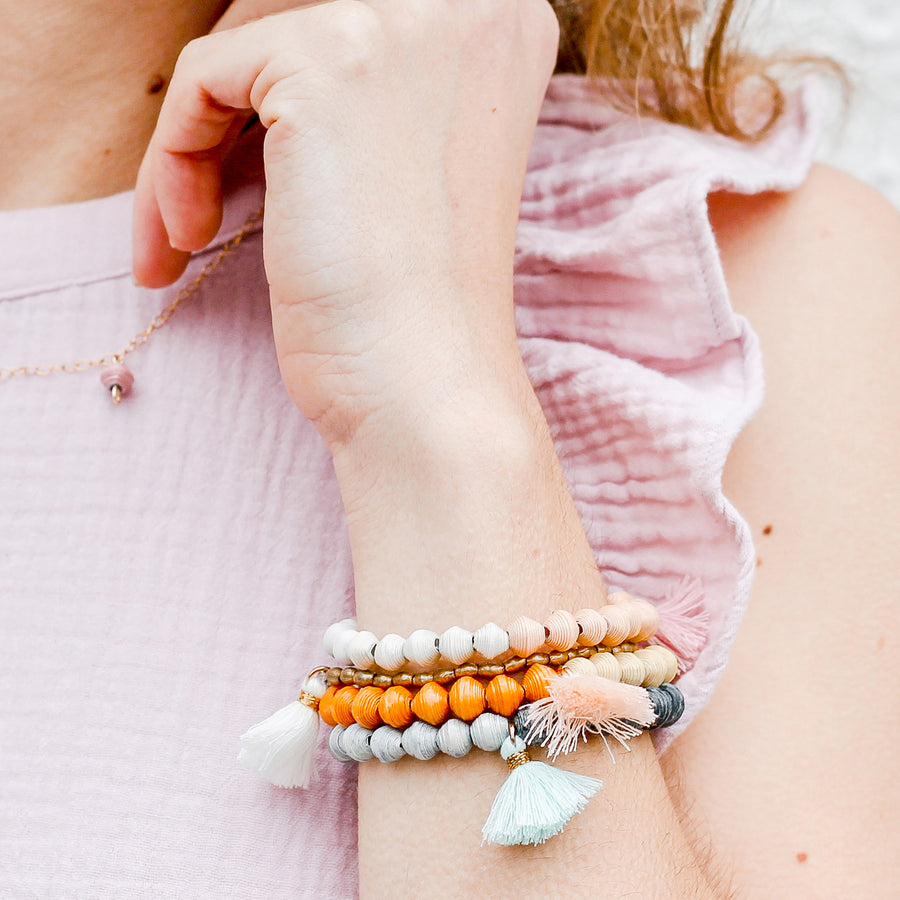 The Jetsetter Tassel Bracelet: yellow and orange handmade paper bead bracelet with tassel made by artisans in the Horn of Africa