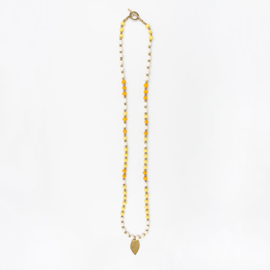 The Leaf Pendant necklace is made with handmade paper beads with brass charm from Ethiopia by artisans in the Horn of Africa