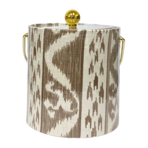 This stylish 3 quart ice bucket features taupe Rapallo fabric from Cowtan & Tout with a plastic coating. The handle is gold metallic and clear acrylic lid is topped with a gold ball.