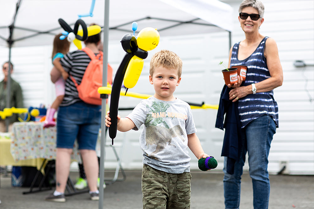 Bees and blueberries festival little boy holding a balloon animal