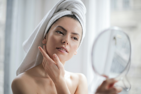 Woman with hair wrapped in towel looks in a mirror and touches her face. Honey can be used as a moisturizing facial treatment.