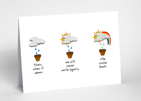 "There is an A6 sized landscape orientated white greetings card. Card shows three plant pots in a horizontal line. The first has a cloud and raindrops above it. The second is the same but the sun has appeared behind the clouds. The third has the sun and a rainbow as well as a cloud, there is slightly less rain and a green shoot has now appeared in the plant pot. The quote underneath the plant pots reads, ""Then, when it seems we will never smile again, life comes back."""