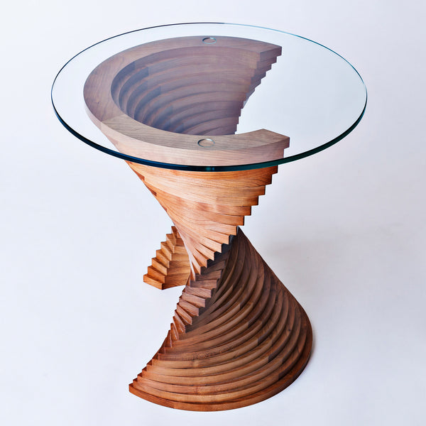 A small glass topped table with a base made of layers of wood twisted in a fan shape.