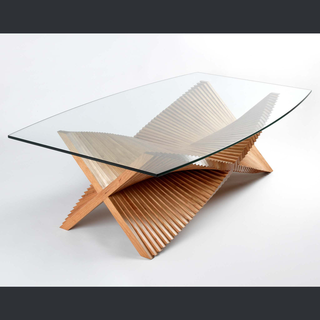 A glass topped coffee table with layered legs in a cross shape