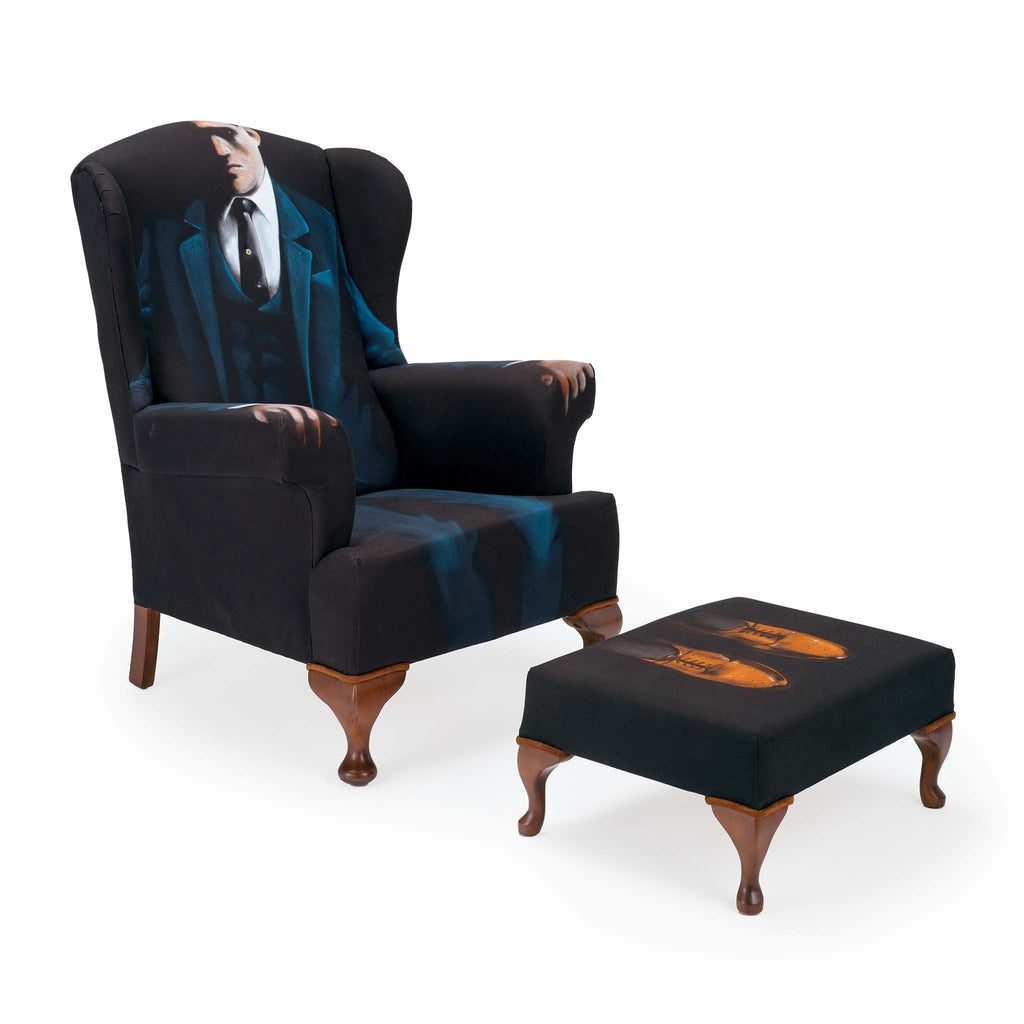 A wing back armchair upholstered with the picture of a gentleman sitting on the chair. His feet are upholstered the footstool.