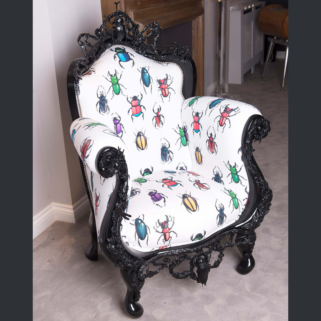 A vintage style armchair of dark brown wood with white upholstery upon which coloured beetles are printed.