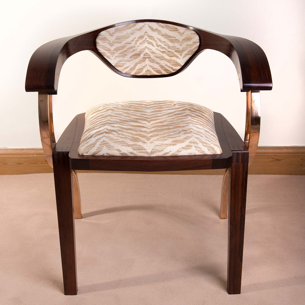 Parlare chair made with Indian rosewood. A round shape with curved legs.