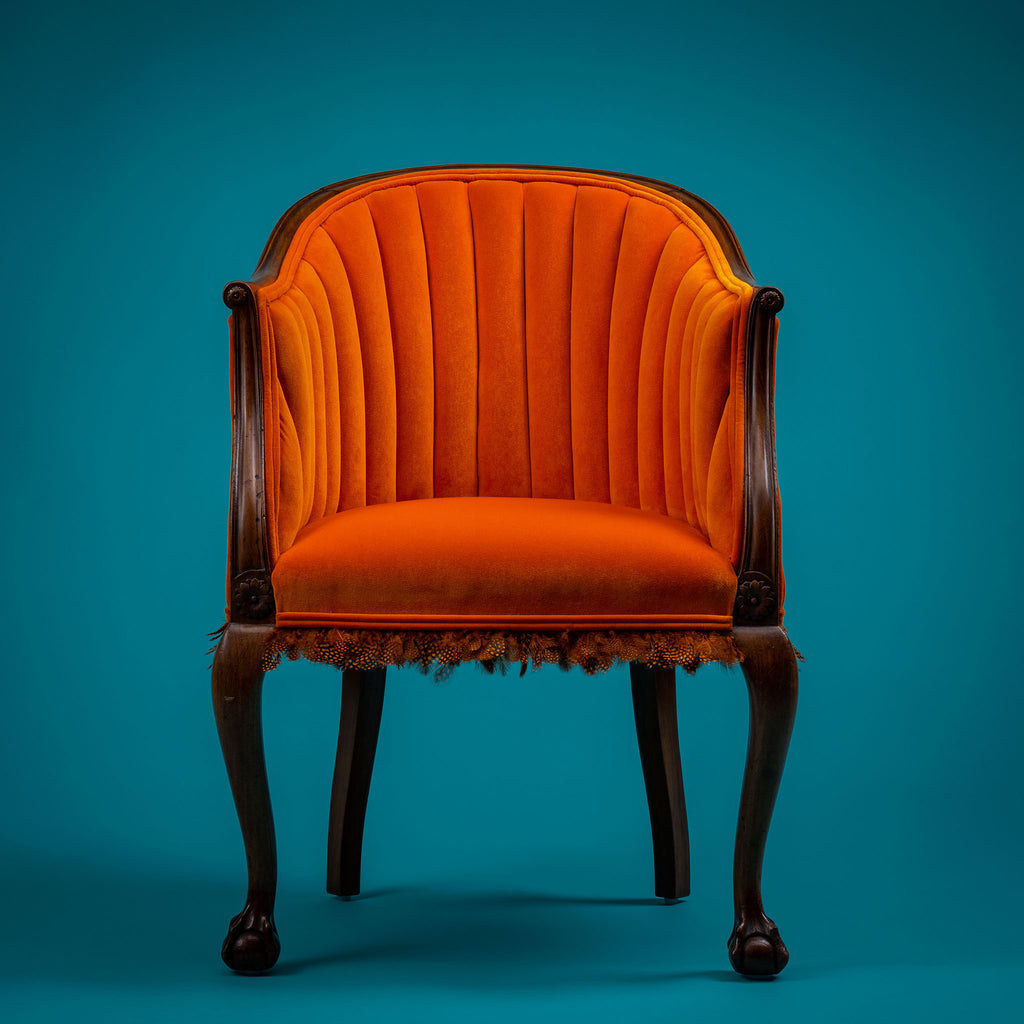 Small orange chair with wooden frame, guinea fowl feathers around the bottom of the seat