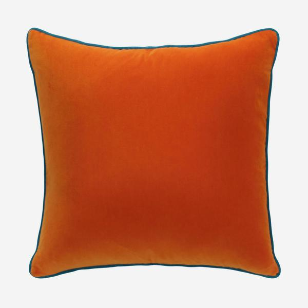 Square orange velvet cushion with turquoise piping around the edge