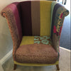 An high backed armchair with high sides, in a patchwork style upholstery
