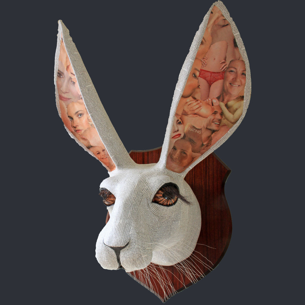 White rabbit made from papier mache mounted on a wooden plaque