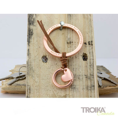 "TROIKA Bag charm ""TEMPTATION"" - gold hanging on wood"