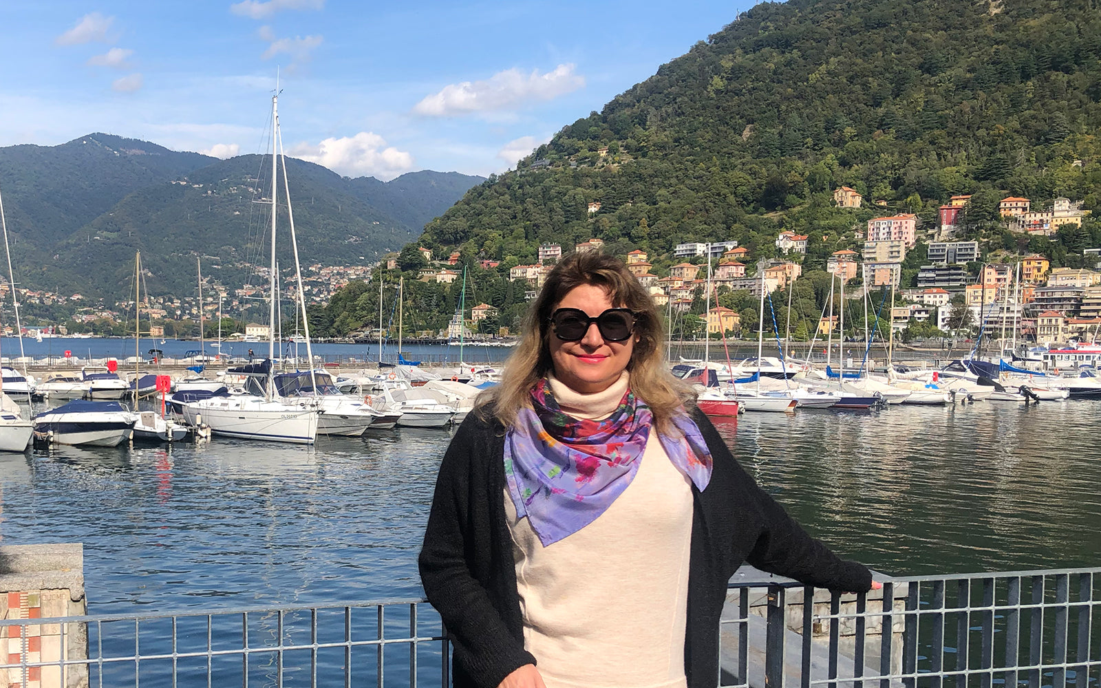 Impressionist artist and silk-scarf designer Oksana Johnson at the harbor in Como, Italy, wearing her Lavender Dream 100% silk scarf, with Lake Como and hills in the background.