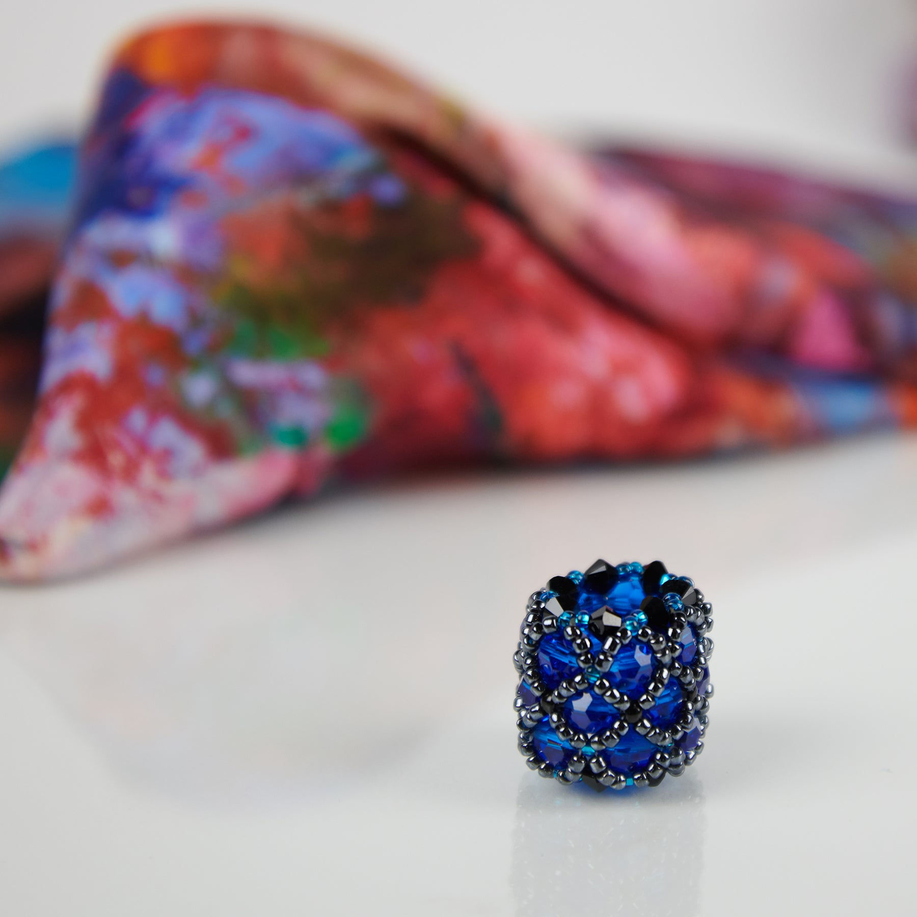 Close-up of blue handmade scarf ring, with an Orange Bouquet 100% silk Italian scarf in background.