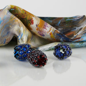 Close-up detail of two blue and one red handmade scarf rings, with a White Magnolias 100% Italian silk scarf.