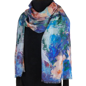Long cashmere-silk scarf with floral design by Oksana Fine Art and Design, based on an impressionist painting of pink orchids with a light green and blue background, worn over a black sweater.
