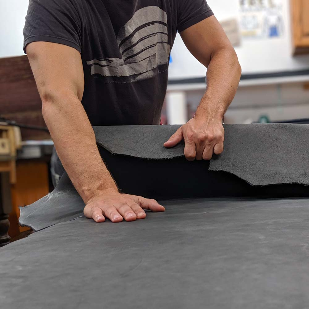 Obscure Belts' Bryan unrolling and inspecting a slate gray full grain leather cow hide