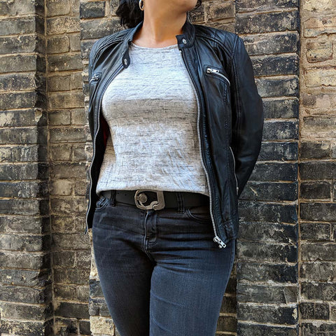 skeleton belt on wife wearing jeans, leather jacket, pair of silver earrings, and a non traditional watch
