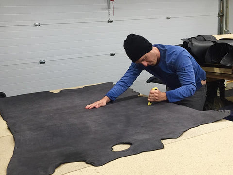 bryan squaring off a leather hide to get it ready to make into handmade belts