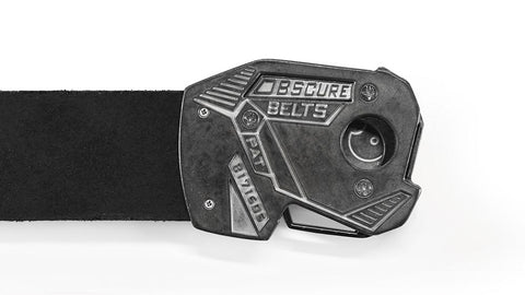 "the back of an angular buckle attached to black leather. The finish is a whitewashed pewter that highlights recessed words ""obscurebelts.com"", a patent number, and cool racing stripes. a logo on the inside of the buckle peeks through a hole in the back."