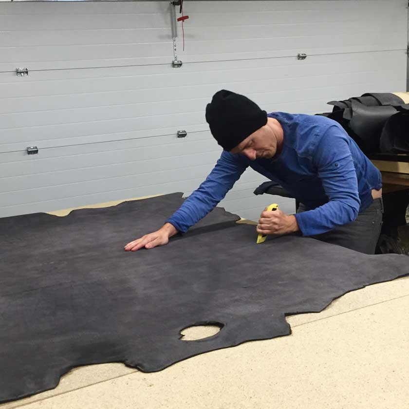 Bryan preparing a hide of gray rough rider leather