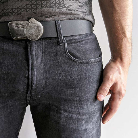 distressed metal belt buckle with black leather belt on dark jeans and a t-shirt