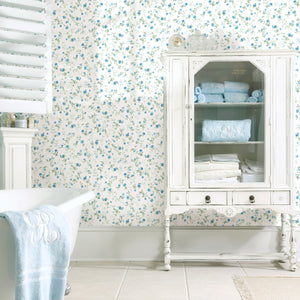 Catlett Blue Floral Toss Wallpaper-Darling blue flowers with leafy green stems are scattered across a white background with a watercolor design.  hung in bathroom