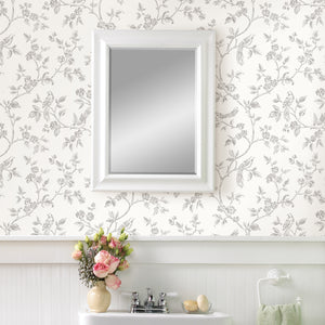Aaron White Bird Trail Wallpaper-Its grey pattern, featuring birds and flowers, pops against an off-white background.  hand-drawn style.  hung over vanity