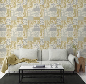 Hammons Gold Block Botanical Wallpaper-features a variety of leaves in gold and silver hues,  Its textured block design is accented by glittering details.   hung in living room