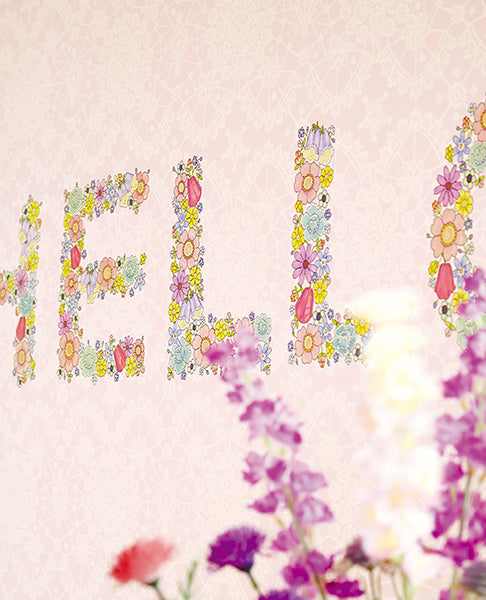 You Had Me At Hello Mural-The letters are made up of brightly colored flowers, complementing the light pink lacy background. close up of flowers on wall