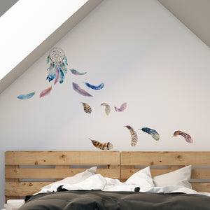 Celestial Dreamcatcher Wall Decal is a peel  and stick wallpaper with purple, pink and blue hues and has white dots on the feathers.  It is hung over a bed.