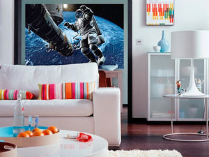 Space Cowboy Wall Mural-an astronaut floating beyond earth with a vast darkness stretching out behind him. hung in living room