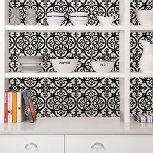 Avignon Peel & Stick Backsplash is a black and white gothic tile that is hung on the wall behind white shelves with dishes